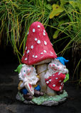 Garden Gnomes. Two garden gnomes learning the red mushroom royalty free stock photography