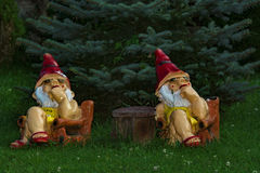 Garden gnomes. Watching and thinking at table in garden Royalty Free Stock Photo