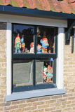 Garden gnomes in window. Garden gnomes and other statues in window stock image