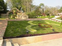 Hyderabad, India - January 1, 2009 Garden with green grass at Ramoji Film City. Garden with green grass, yellow, red, brown plants, trees and flowers at Ramoji royalty free stock photos
