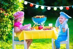 Garden grill party for kids. Children grilling meat. Family camping and enjoying BBQ. Brother and sister at barbecue preparing steaks and sausages. Kids eating Stock Images