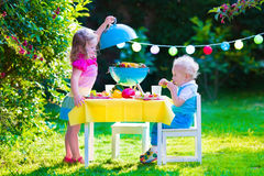 Garden grill party for kids. Children grilling meat. Family camping and enjoying BBQ. Brother and sister at barbecue preparing steaks and sausages. Kids eating Royalty Free Stock Photos