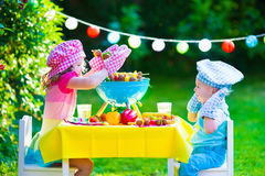 Garden grill party for kids. Children grilling meat. Family camping and enjoying BBQ. Brother and sister at barbecue preparing steaks and sausages. Kids eating Royalty Free Stock Photo