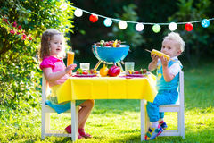 Garden grill party for kids. Children grilling meat. Family camping and enjoying BBQ. Brother and sister at barbecue preparing steaks and sausages. Kids eating Stock Photos