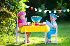 Garden grill party for kids. Children grilling meat. Family camping and enjoying BBQ. Brother and sister at barbecue preparing steaks and sausages. Kids eating Royalty Free Stock Photography
