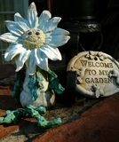 Garden Guardian. Smiling garden sculpture and welcome sign Royalty Free Stock Images