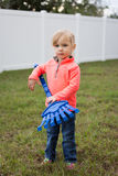 Garden Helper. Cute little girl helping with yardwork by using her blue toy rake stock photos