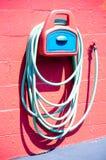 Garden hose. Green garden hose on a red wall house stock photography