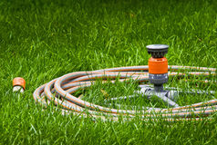 Garden hose. At the green grass background. Watering pipe and lawn sprinkler - water gardening tools stock photos