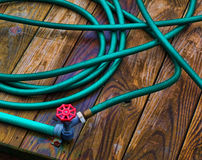 Garden Hose. Green garden hose and red spiget coiled on a wooden dock stock photography