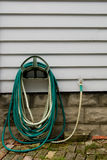 Garden Hose. A coiled garden hose on the side of a building stock images