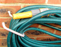 Garden hose on brick wall Royalty Free Stock Photo
