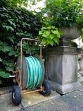 Garden hose cart. A hose cart in a city garden near a stone flower vase Stock Image