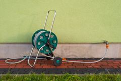 Garden hose connected to a tap protruding from a building against a background of light green facade. royalty free stock photography