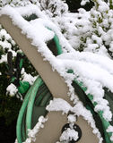 Garden hose covered in snow Royalty Free Stock Images