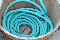 Garden Hose curled in Wooden bucket. For garden royalty free stock photos