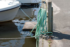 Garden hose on the docks. A green gaarden hose attached to water is available to boat owners to clean off their boats when the dock royalty free stock image