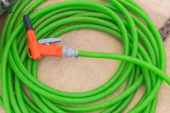 Garden hose. Green with orange spray hose at the end of stock photography