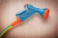 Garden hose hand spray gun on wooden board gardening concept.  royalty free stock images