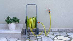Garden hose for irrigation near the house wall stock photos