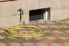 Garden hose laying on pavement with weed and with dirty old wind. Hose pipe with faucet from wall of house, hose laying on pavement with weed, with dirty old royalty free stock image