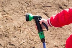 Garden hose in little child hand. Garden hose in a little child hand stock photos