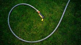 Garden hose lying on green grass at garden. Garden hose lying on fresh green grass at garden royalty free stock photos