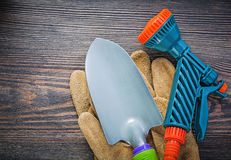 Garden hose nozzle protective gloves hand spade on wooden board. Agriculture concept royalty free stock images