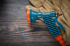 Garden hose nozzle protective gloves on vintage wood board agric. Ulture concept royalty free stock photography