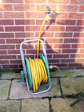 Garden hose reel. A garden hosepipe connected to the tap ready for use royalty free stock images