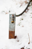 Garden hose and spout in the snow. Garden hose and spout covered in snow in winter royalty free stock images