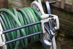 Garden hose and spray nozzle on a reel. Old garden hose and spray nozzle on a reel Stock Image