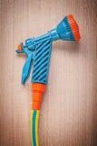 Garden hose with water sprayer on wooden board gardening concept.  stock photos