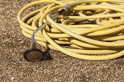 Garden Hose. Yellow garden hosepipe and sprayer attachment royalty free stock photos