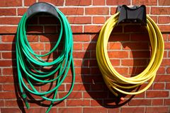 Garden Hoses on a Brick Wall royalty free stock image