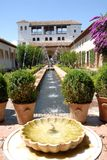 Garden with hot fountain of the Alhambra in Granada in Spain. Photo taken inside the Alhambra in Granada in Spain. The picture shows a long, narrow garden to the Stock Photography