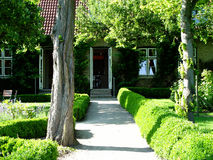 Garden + house. Garden of a restaurant, path leading to the house Royalty Free Stock Photography
