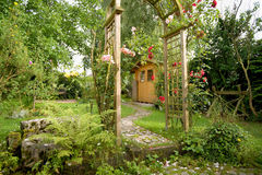 Garden idyll. With a garden shed and rose arch with blooming red roses royalty free stock images