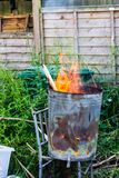 A garden incinerator bin rested on a metal chair frame burning scrap wood stock images