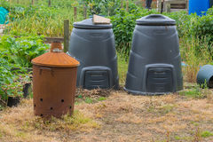 Garden incinerator and black compost bins Royalty Free Stock Image