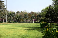 Garden in India. Raj Ghat is a place of Ghandi cremation in India adjoining a beautiful garden. Green meadow, multicolored flowers, royal palms, sunny day Royalty Free Stock Photography