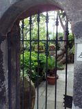 A garden in Massalubrense, sud Italy. A part of a garden in Massalubrense, near Sorrento in Italy seen through the entrance gate, supported by an ancient stone Stock Photography