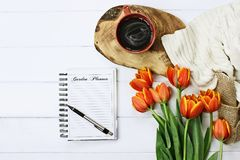Garden Journal and Coffee. Overhead shot a garden journal notebook with pen, coffee and a bouquet of orange and yellow tulips over a wood table. Flat lay top Stock Images