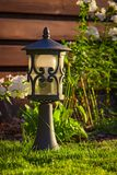 Garden lamp, made in the Middle Ages, on a lawn with a juicy green grass.  royalty free stock photography