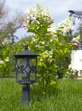 Garden lamp, made in the Middle Ages, on a lawn with a juicy green grass.  stock image