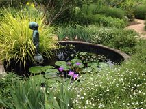 Garden landscape design with a pond and a statue of a boy Royalty Free Stock Images