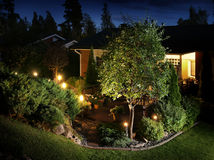 Garden lights illumination. Home garden evening illumination electric lights on garden patio Royalty Free Stock Photos