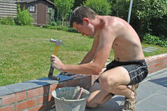 Garden masonry. Young man in naked upperbody putting tiles on a little wall Stock Photography