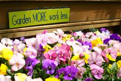 Garden More, Work Less. A sign in a flower nursery urges people to do more gardening and work less Stock Images