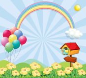 A garden near the hills with balloons, a rainbow and a pet house Royalty Free Stock Images